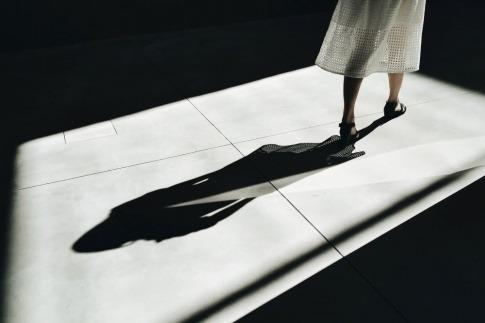 Eine Frau geht vor ihrem Schatten weg