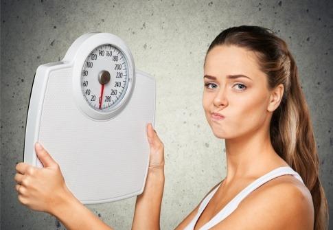 Eine Frau hält eine Waage und hat ihr Wohlfühlgewicht noch nicht erreicht