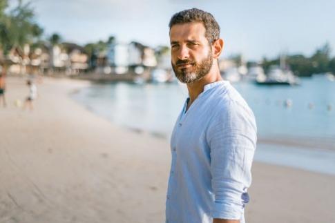 Ein Mann am Strand schaut in die Kamera und redet nicht