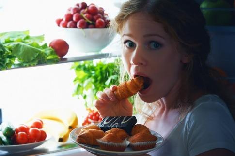 """Die Frau, die in diesem Bild vor dem Kühlschrank kniet und ungesunde Snacks isst, hat die Antwort auf die Frage """"was soll ich kochen?"""" für sich selbst bereits beantwortet. Doch gesund essen geht auch mit wenig Zeitaufwand."""