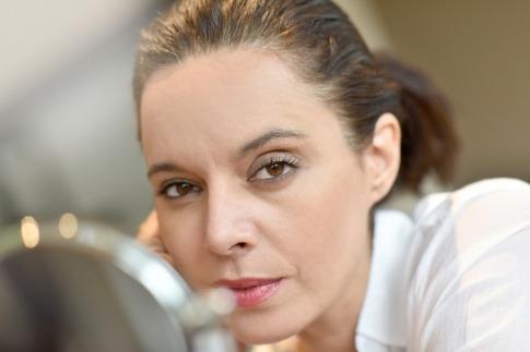 Eine Frau mit Augenringen sieht in den Spiegel