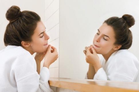 Eine Frau begutachtet ihre Pickel in einem Spiegel