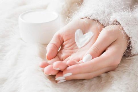 Eine Nahaufnahme der ineinander gelegten Hände einer Frau. Auf der linken Hand liegt ein Herz aus pflegender Creme.
