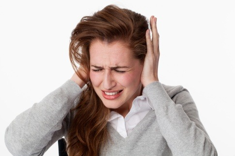 Eine Frau hält sich die Ohren zu und fragt was tun gegen Tinnitus