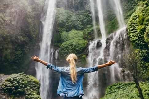 Eine Frau steht vor einem Wasserfall