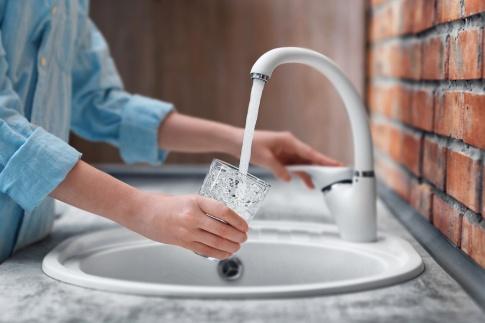 Eine Frau lässt Leitungswasser in ein Glas laufen.
