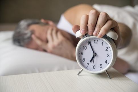 Mann im Bett greift auf Wecker