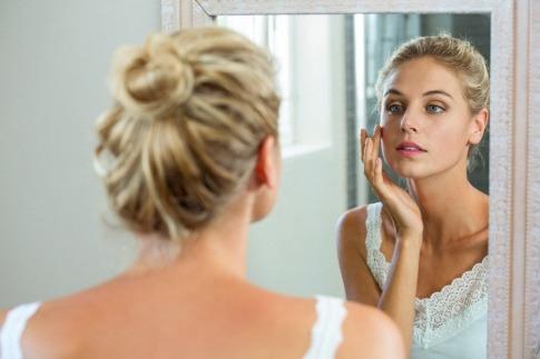 Junge Frau betrachtet Haut skeptisch im Spiegel.