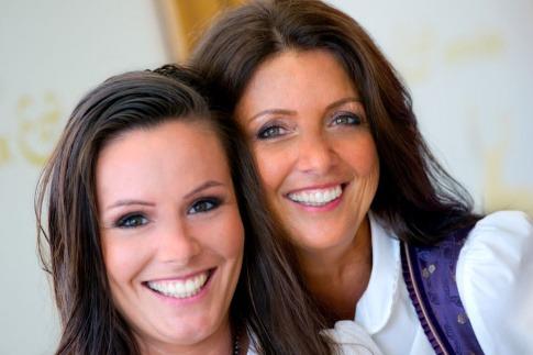 Zwei Frauen mit weißen Zähnen lächeln