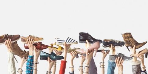 Hände halten viele Schuhe