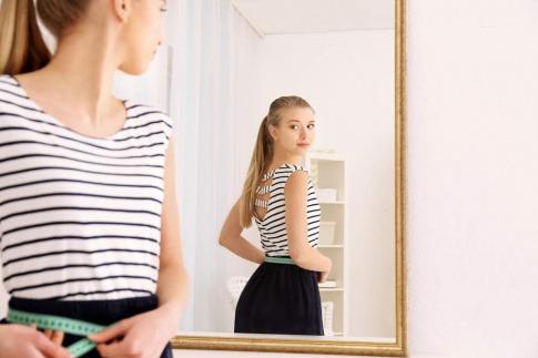 Frau schaut in den Spiegel mit Maßband um die Hüften.