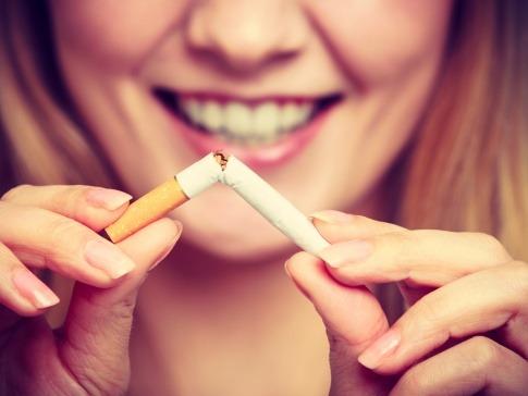 Eine junge Frau knickt eine Zigarette ab und wird zum Nichtraucher