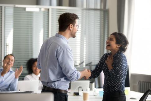 Teamleader zeigt Wertschätzung gegenüber Mitarbeiterin durch Handschlag
