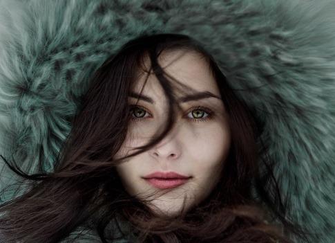 Eine Frau hat eine dicke Kapuze über ihre langen Haare