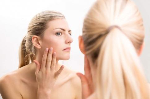 Frau vor dem Spiegel testet die Wirkstoffaufnahme