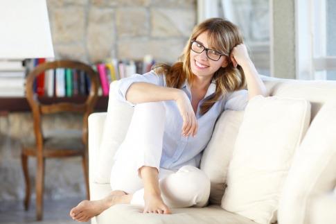 Eine Frau hat sitzt voll Würde und ausgeglichen auf einer Couch