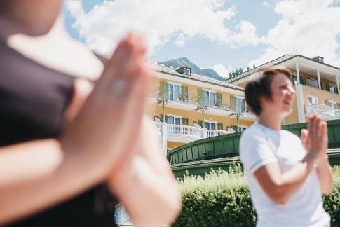 Zwei Frauen machen Yoga vor dem Alpenhaus Gasteinertal