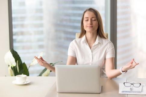 Frau sitzt vor ihrem Laptop ohne Stress und meditiert
