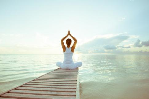 Eine Frau sitzt am Ende eines Stegs und entspannt mit Yoga