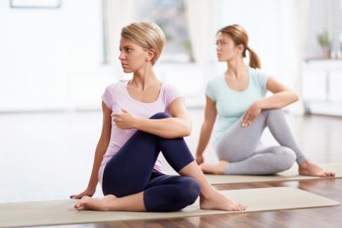 Zwei Frauen führen eine Yoga Übung zur Entspannung durch