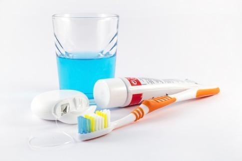Utensilien zum Zähne putzen wie Zahnbürste, Zahnpasta und Zahnseide liegen nebeneinander