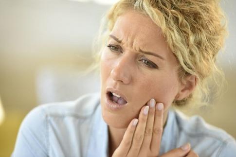 Eine Frau hat offensichtlich Zahnschmerzen, ev. Parodontose