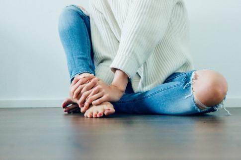 Eine Frau mit geschnittenen roten Zehennägeln sitzt am Boden