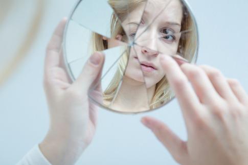 Das Spiegelbild einer Frau ist auf einem zerbrochenen Spiegel