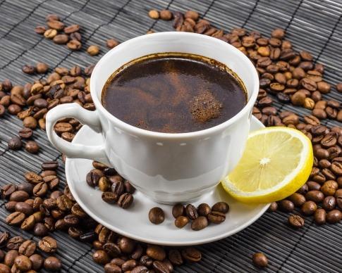 Es wird frischer Zitronensaft in eine Tasse Kaffes gepresst