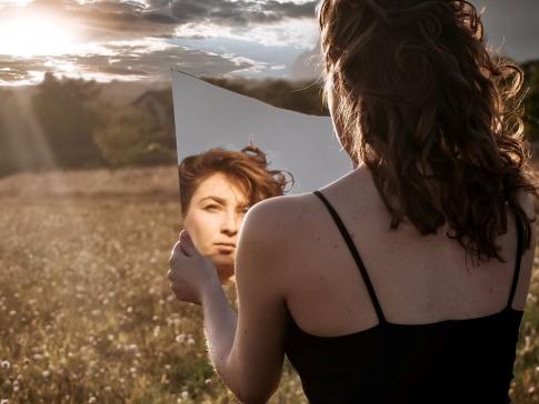 Frau, die mit einerm Spiegel ihre Zornesfalte glätten will