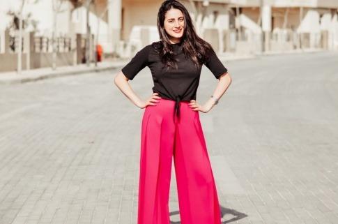 Eine Frau trägt elegenate rote Marlenehosen