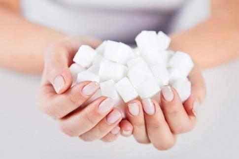 Frau hält Zuckerwürfel in Händen.