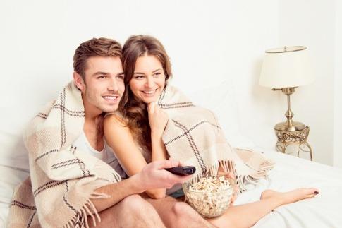 Ein Paar sitzt zufrieden mit einer Fernbedienung