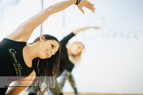 Zwei Frauen tanzen, im Hintergrund eine Pole Dance Stange