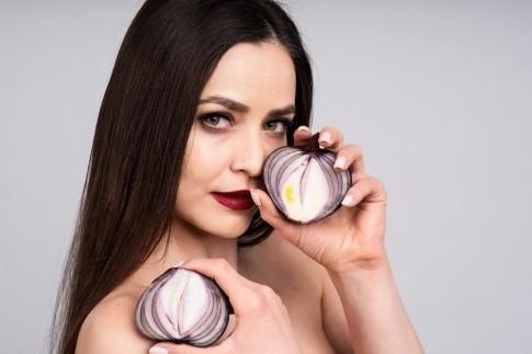 Frau hält eine Zwiebel gegen Pickel