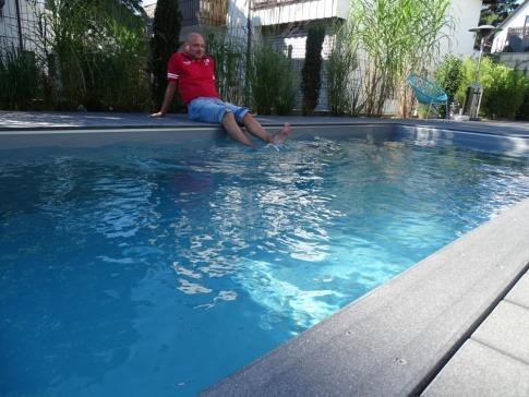 Ein Mann entspannt sich bei einem Schwimmbecken