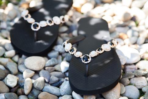 schwarze Zehensandalen auf kleinen Steinen