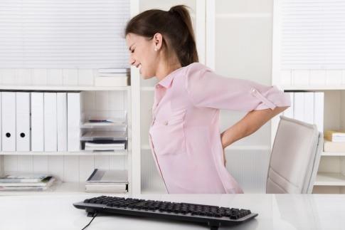 Eine Frau, die im Büro ist und von Rückenschmerzen geplagt wird