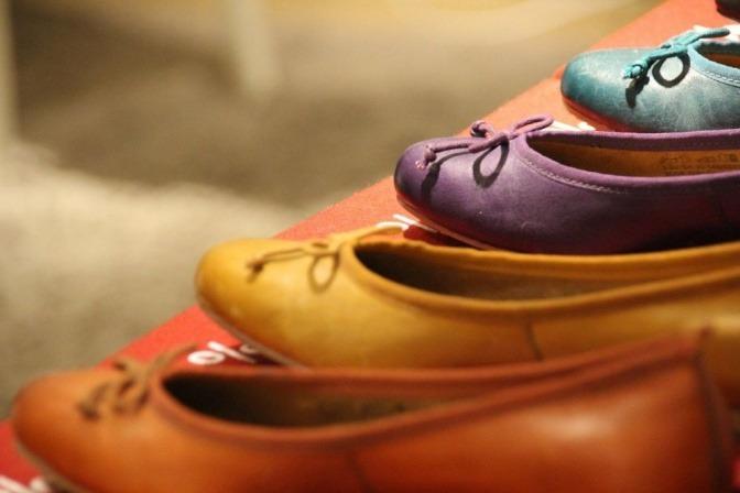 Auf einer roten Schachtel stehen Ballerina Schuhe in verschiedenen Farben