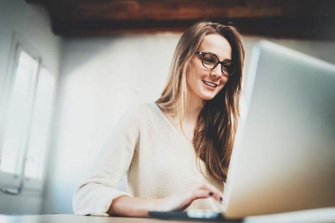 Eine junge Frau sitzt in einem Büro an ihrem Laptop und arbeitet. Sie wirkt motiviert und zufrieden.