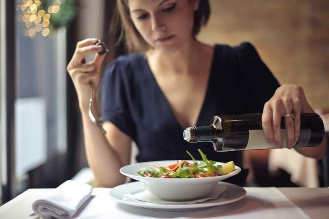 Eine Frau isst Salat, damit sie vom Mittagstief verschont bleibt
