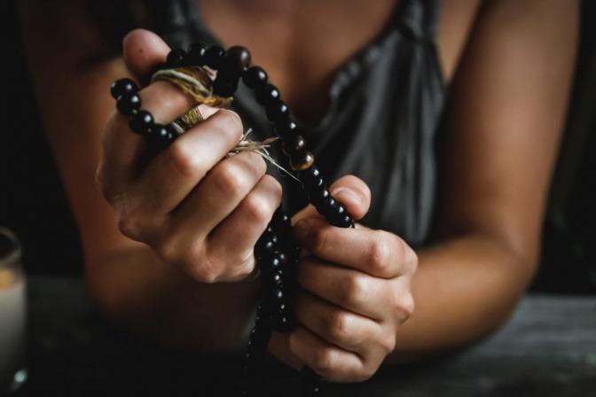 Eine Frau hält einen Rosenkranz in der Hand