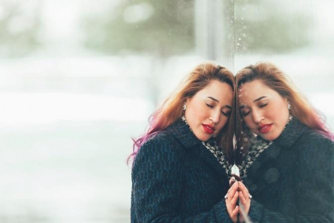 Eine Frau umarmt ihre Spiegelung