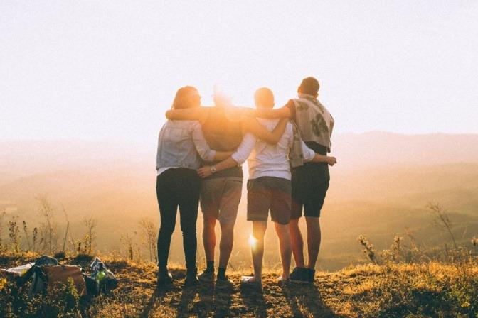 Vier Freunde stehen eng umschlungen im Licht es Sonnenuntergangs