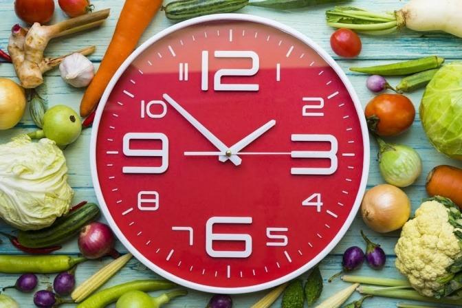 Eine Wanduhr, die kurz vor Zwei anzeigt, liegt inmitten einer Ansammlung von Obst und Gemüse.