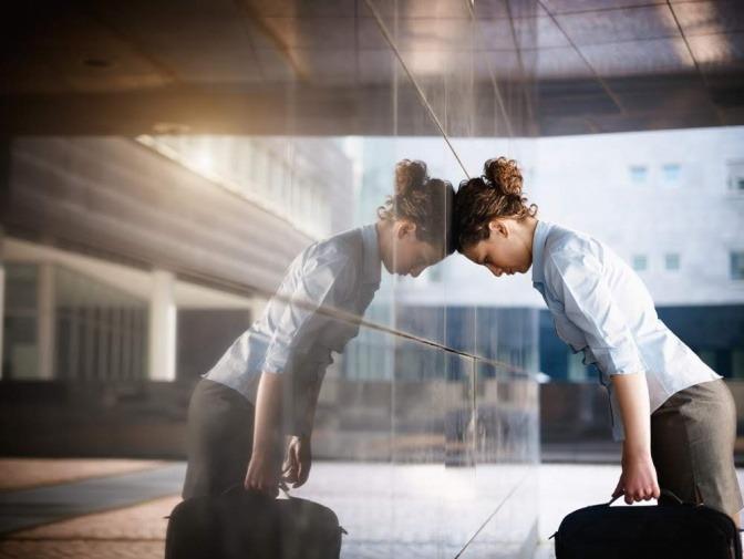 Eine Frau steht mit leicht gebeugtem Oberkörper vor einer Wand, ihr Kopf lehnt dagegen.