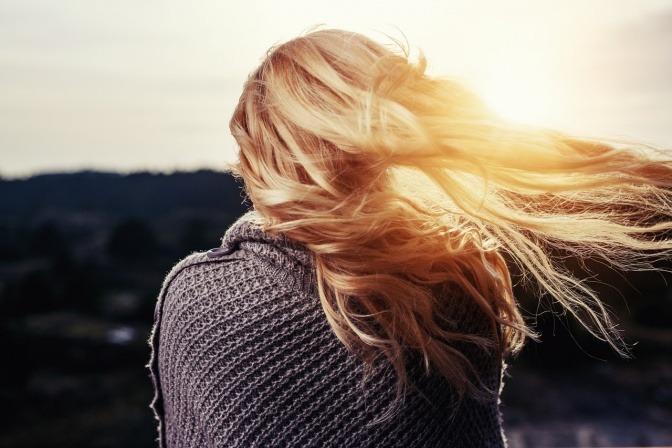 Eine Frau mit prachtvollen, blonden langen Haaren steht mit dem Rücken zum Betrachter gewandt und betrachtet einen Sonnenuntergang, während ihre Haare im Wind fliegen.