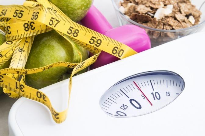 Eine Waage und kohlenhydratarme Lebensmittel sind bei einem Maßband