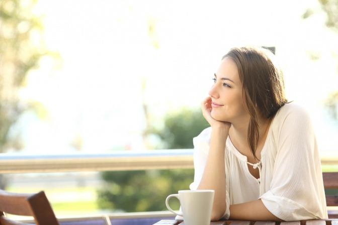 Eine Frau schaut durch Access Consciousness glücklich aus