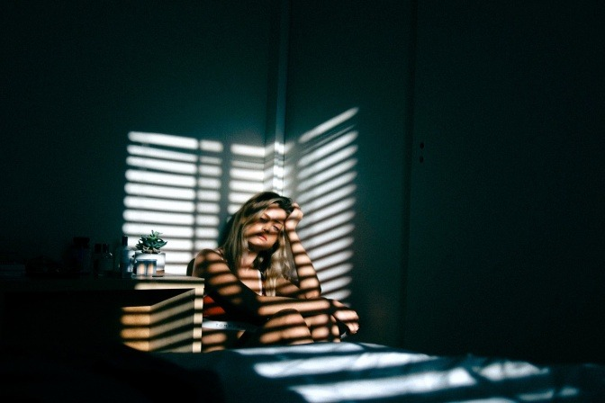 Eine ängstliche Frau sitzt im Bett